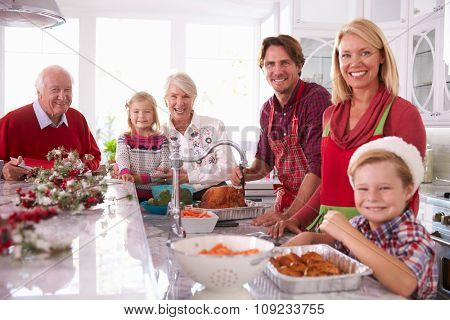 Extended Family Group Basting Christmas Turkey In Kitchen