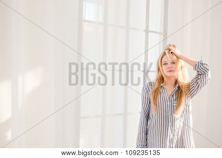 Carefree relaxed beautiful young female with tousled hair in striped pajamas standing near big window