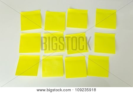 Closeup Of 12 Blank Yellow Sticky Notes On White Board