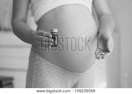 Black And White Shot Of Pregnant Woman Holding Vitamins In Pills