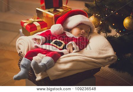 Toned Photo Of Newborn Baby Dressed In Santa Costume Lying With Christmas Gifts
