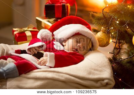Baby Boy In Santa Costume Sleeping At Fireplace Next To Christmas Tree