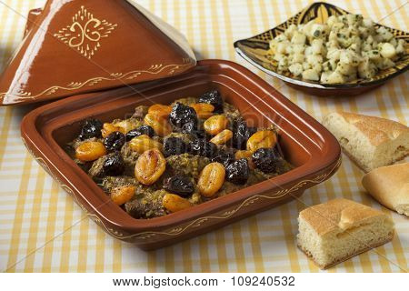 Square tagine with apricots and prunes, potato salad and bread