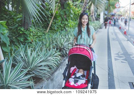portrait of woman take a walk with her baby inside the baby stroller poster