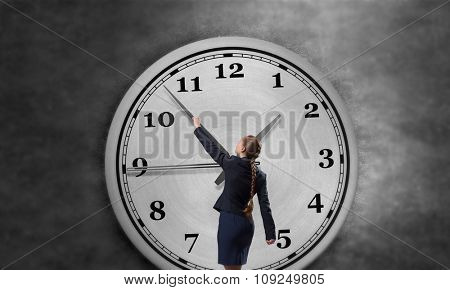 Rear view of businesswoman moving arrow on clock