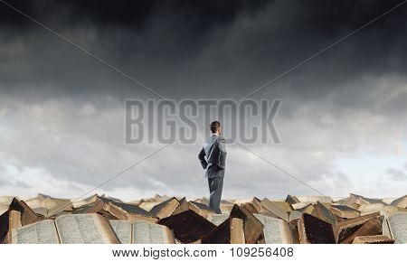Young confident businessman with arms on waist standing on pile of old books  poster
