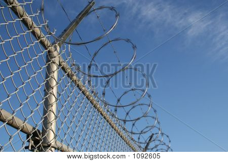 a barbed wire fence on a bright clear day. poster