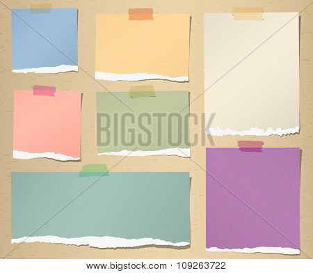 Set of various colorful torn note papers with adhesive tape on brown background