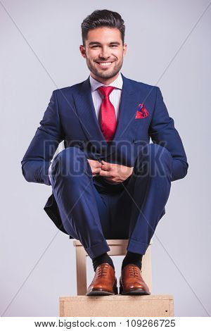 hansome business man sitting on a chair while unbuttoning his jacket