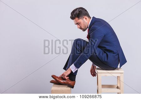 handsome man in suit sitting on chair in studio cleaning his brogue shoes