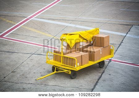 Airport vehicle transporting air cargo  to airplane on runway