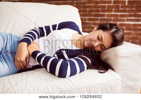 Asian woman lying on the couch with cramps at home in the living room