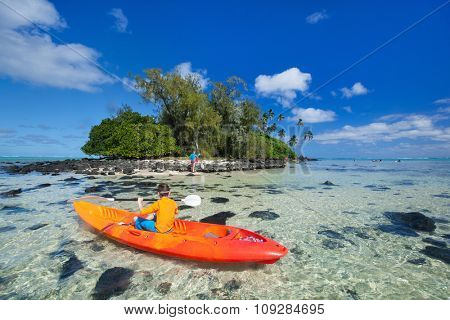 Happy teenage boy on a kayak at tropical lagoon in fron of exotic island