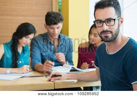 Closeup shot of young man looking at camera. Male student preparing university exam. Portrait of guy with eyeglasess with others students studying in background.
