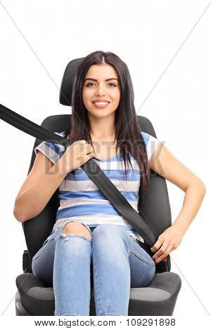 Vertical studio shot of a young woman sitting on a car seat fastened with a seatbelt isolated on white background