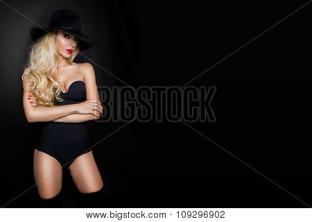 Beautiful blond woman girl sexy model dressed in black lingerie outfit body swimsuit and black hat a
