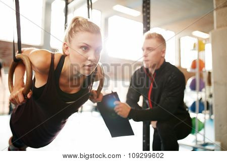 Woman With Her Personal Trainer Exercising On Gymnastic Rings