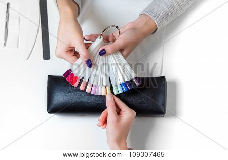 Woman selects yellow color shellac for nail