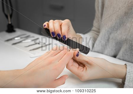 Manicure process with nail file in beauty salon
