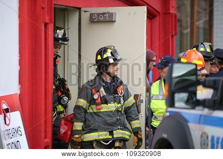 Firefighters in gear exit building
