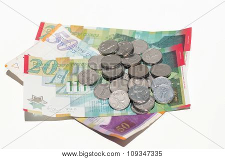 A pile of coins and banknotes of New Israeli Shekels (NIS)