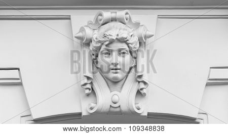 decorative statue of a woman on a building.