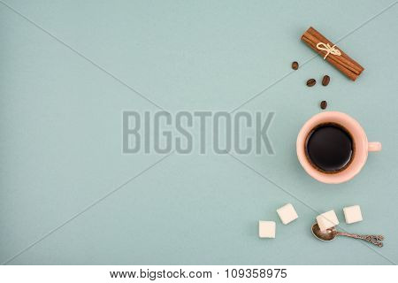 Coffee and in vintage cup with cinnamon and shugar on turquoise background. Top view, copy space.