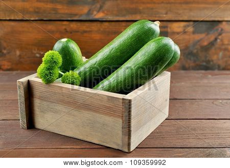 Fresh zucchini in box on wooden background