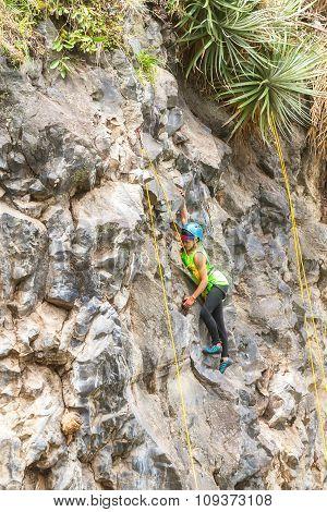 Latin Girl Climbing A Vertical Rock Wall