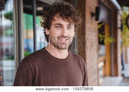 Portrait of happy handsome positive attractive curly smiling young man in brown sweetshirt in the city