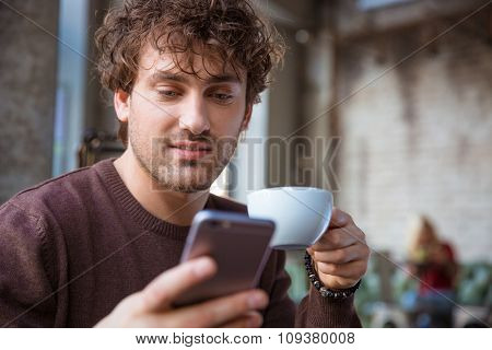 Attractive young curly handsome man in brown sweetshirt  using mobile phone and drinking tea