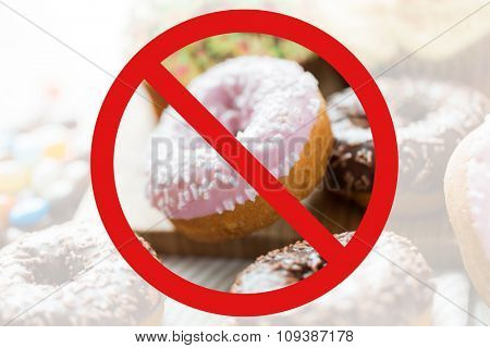 fast food, low carb diet, fattening and unhealthy eating concept - close up of glazed donuts behind no symbol or circle-backslash prohibition sign