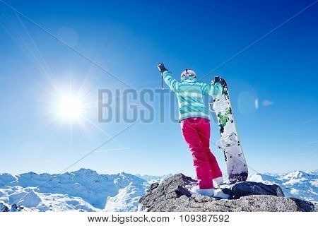 Back view of female snowboarder wearing blue jacket, gloves and pink pants standing with snowboard in right hand and raising left arm against sunny alpine mountain landscape - winter sports concept