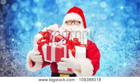 christmas, holidays and people concept - man in costume of santa claus with gift boxes over blue holidays lights background