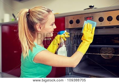people, housework and housekeeping concept - happy woman with bottle of spray cleanser cleaning oven at home kitchen