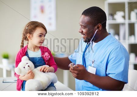 Cute girl with teddybear listening to her doctor