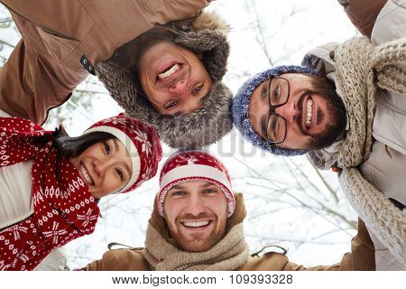 Young cheerful friends in winterwear looking at camera