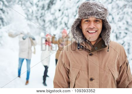 Happy guy in winterwear looking at camera with his friends playing snowballs on background
