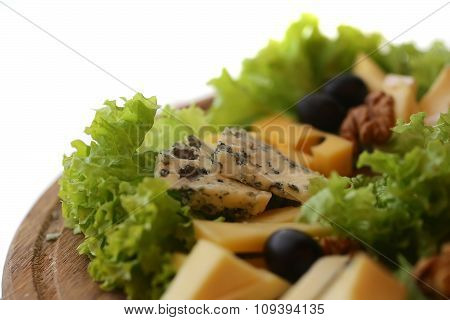 Photo closeup of various types of gourmet cheese slices triangles with mold green salad black olives and walnuts on wooden platter over blurred background horizontal picture poster