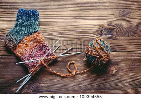 Knitted Sock, Ball Of Yarn And Knitting Needles On A Wooden Surface