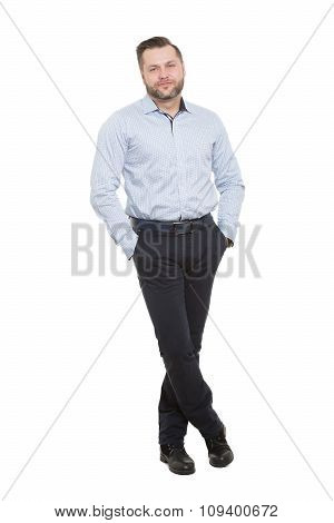 adult male with a beard. isolated on white background. hands in his pockets. legs crossed body langu