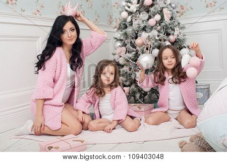 Happy woman with two girls in front of the Christmas tree among gifts