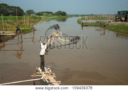 Fishing with cast net in river.