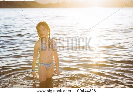 Cute Little Girl In Swimsuit Standing In The Sea Water On The Beach, Sunset In The Bay Of Sharm El S