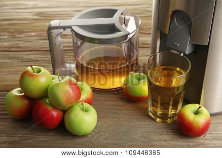 Stainless juice extractor with apples on wooden background, close up