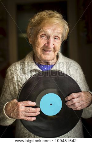 Grandma with Vinyl record disk in the hands. Music background. Space for your text on LP.