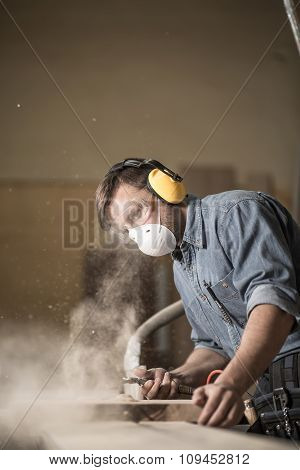 Photo of joiner labouring in mask and glasses for safety poster