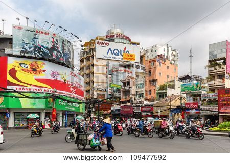 HO CHI MINH, VIETNAM, FEBRUARY 24, 2015 : View on the traffic motorbike and a traditional peddler at a large crossroad in Ho Chi Minh City (saigon), Vietnam