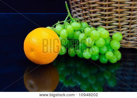 Fresh Orange And Grape Near Wooden Basket