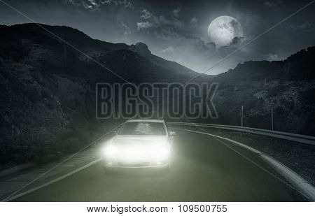 Driving on an asphalt road towards the headlights of car at night
